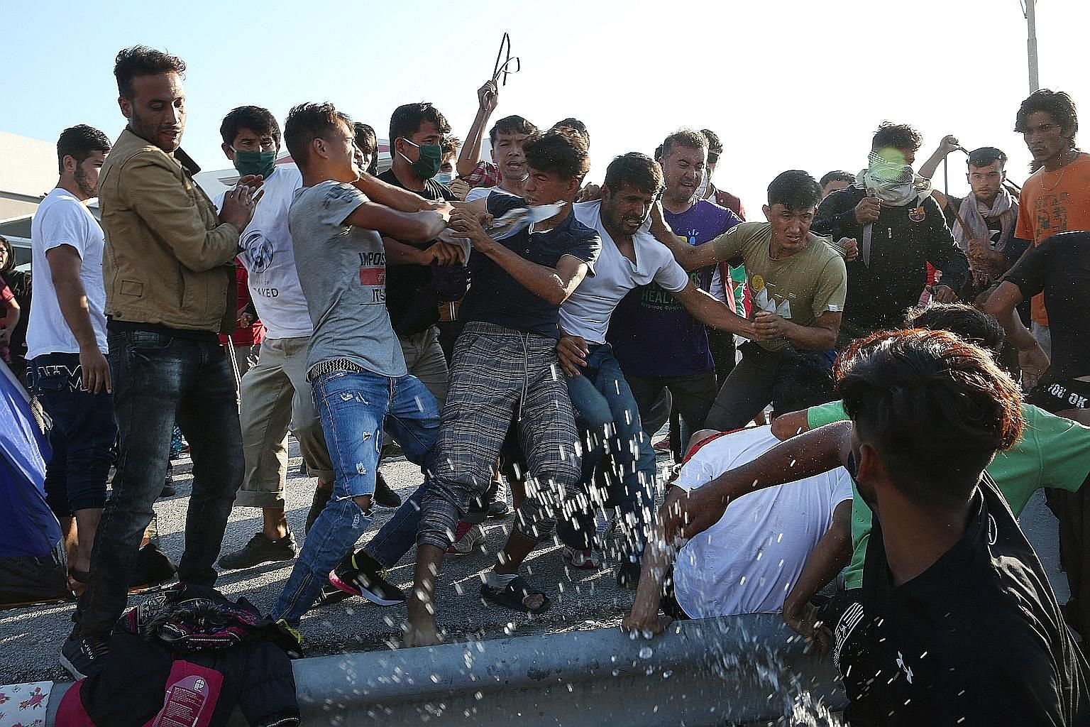 Asylum seekers tussling over a mobile charger near the razed Moria refugee camp in Greece on Wednesday. The camp, with its poor living conditions, had hosted more than 12,000 migrants, four times its stated capacity.