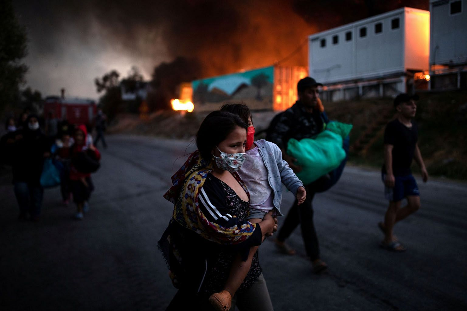 Refugees and migrants fleeing the fire at the Moria camp on the Greek island of Lesbos on Wednesday. The EU's migrant dilemma and consequent humanitarian disasters, the writer says, will not be fixed unless and until the bloc strong-arms its saboteur