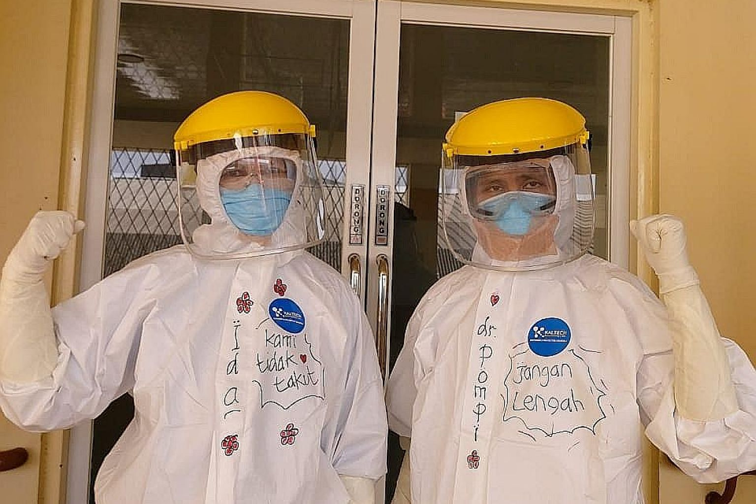 "Pulmonologist Pompini Agustina Sitompul (at right) at the Sulianti Saroso Infectious Diseases Hospital in Jakarta. She is wearing a protective suit on which is written ""Don't be careless"", while her colleague's suit reads ""We are not afraid"". PHOTO:"