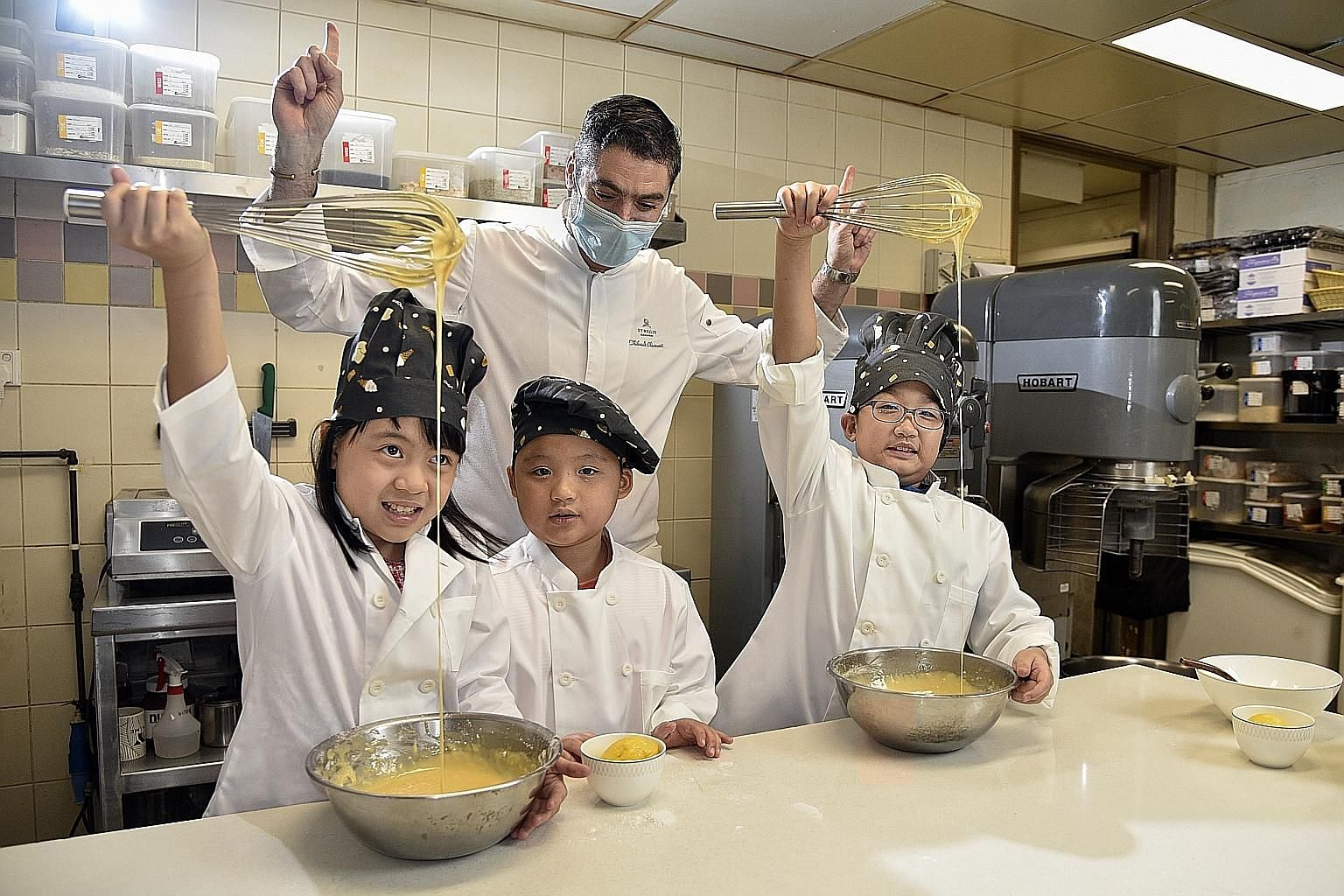 St Regis Singapore's executive chef Thibault Chiumenti guiding a Madeleine-making session and teaching kids to whisk and fold the batter. The St Regis Singapore lobby (above). The interiors of the hotel display old-world palatial charms. A teepee pad