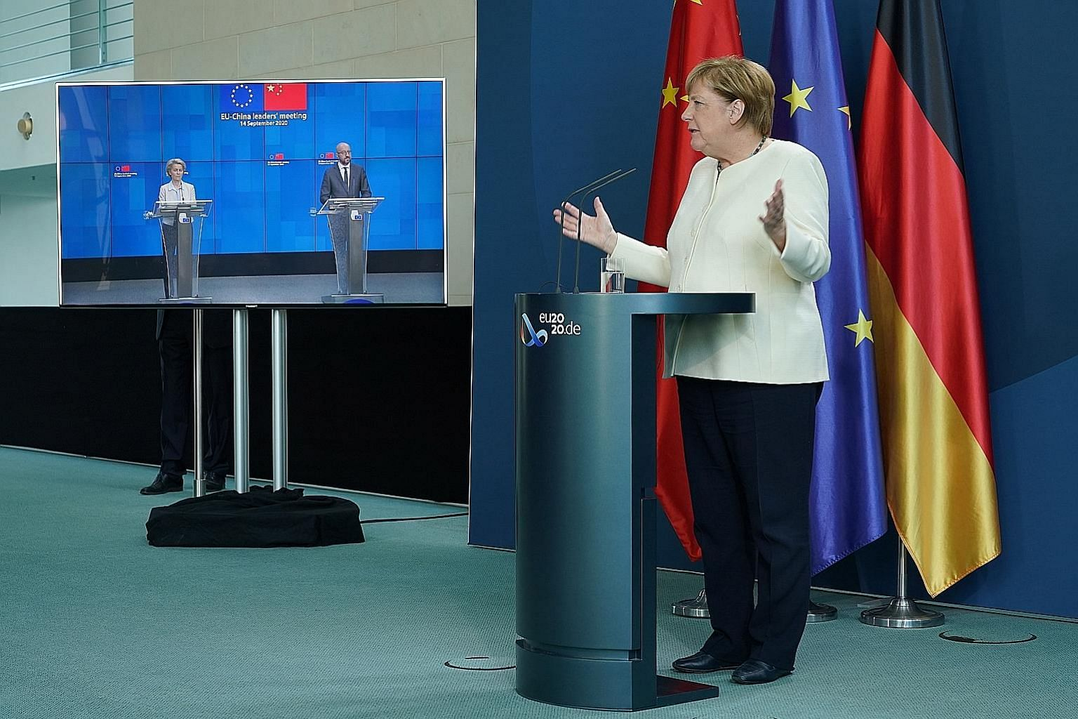 German Chancellor Angela Merkel (right), along with European Commission president Ursula von der Leyen and European Council president Charles Michel (both tuning in via video-link from Brussels), speaking to the media following a video-linked meeting