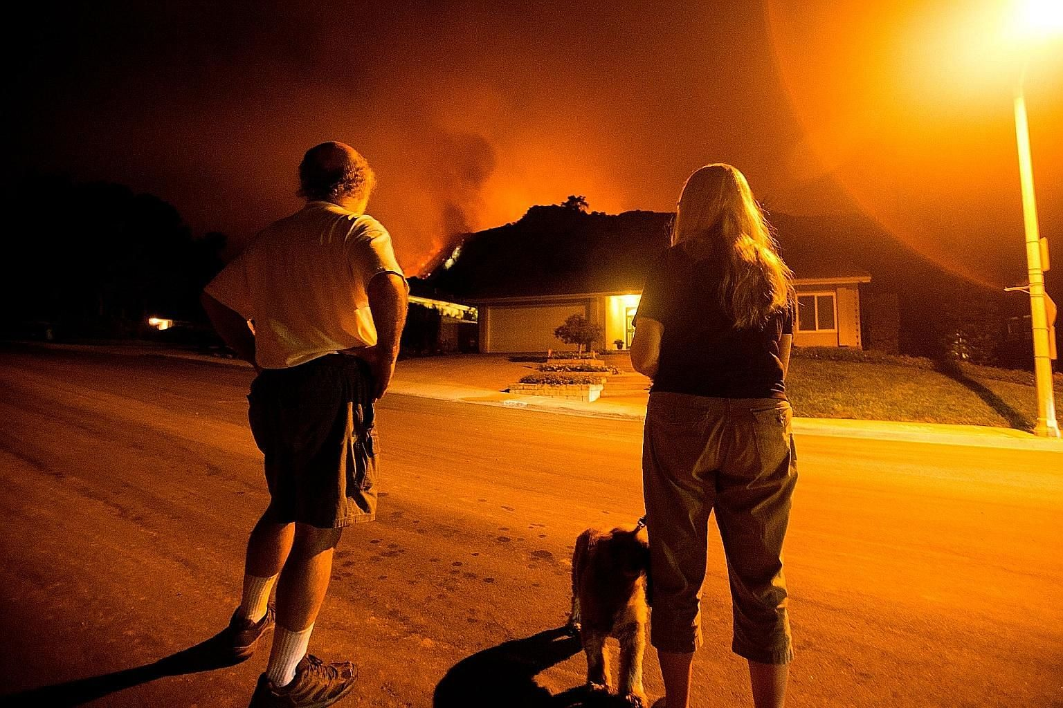 The Bobcat Fire burning on hillsides behind homes on Tuesday in Monrovia, outside Los Angeles in California.
