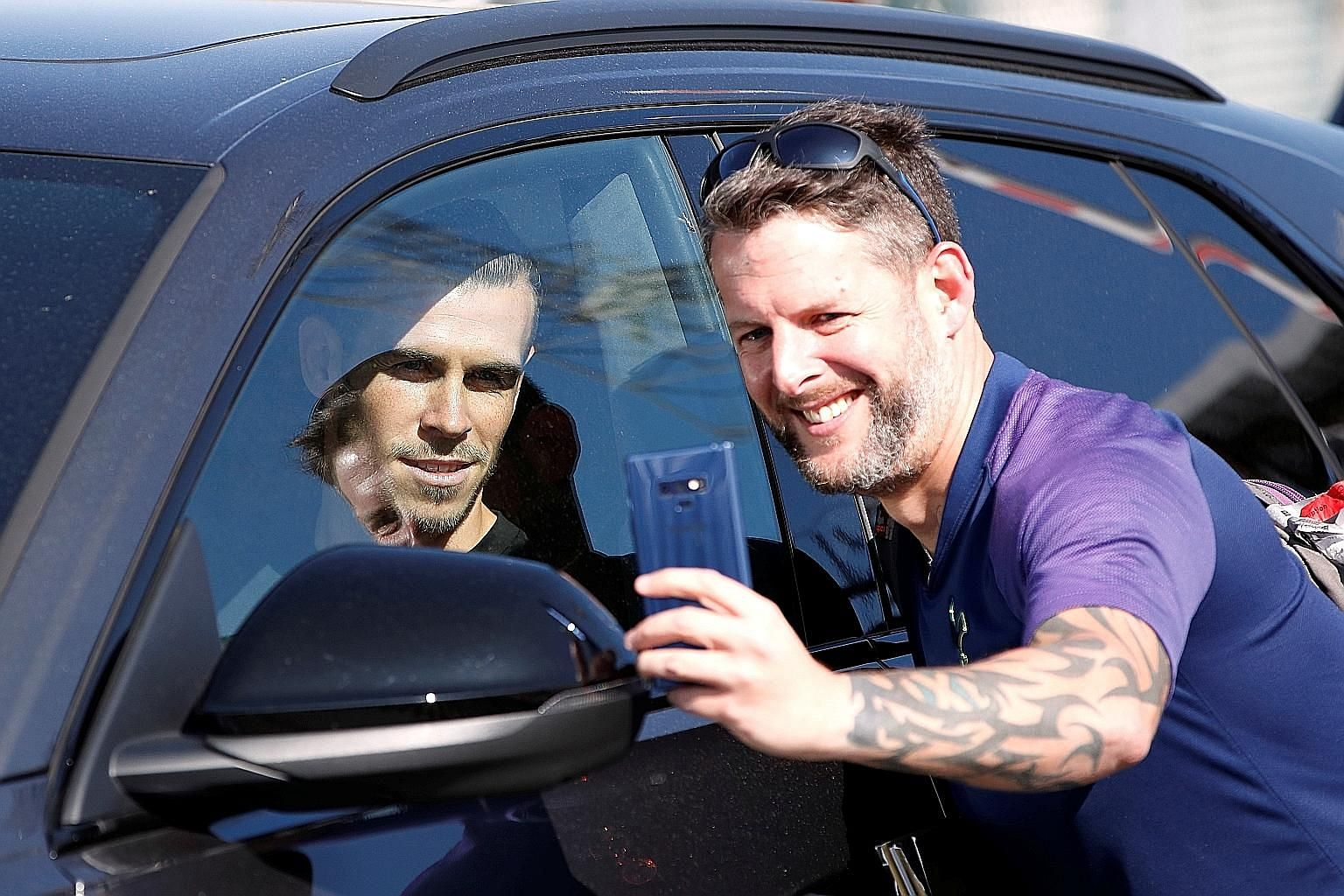 Gareth Bale posing for a wefie with a fan as he leaves Luton Airport yesterday. The Wales forward was expected to join his former club, Tottenham Hotspur, initially on loan. He had left Spurs for Real Madrid in 2013.