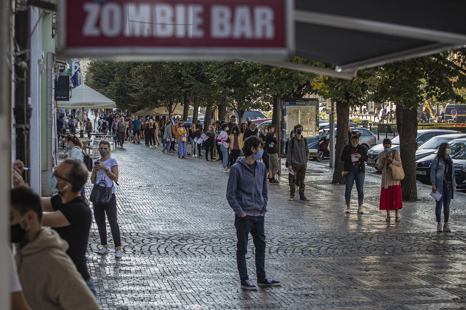 A street in Palma de Mallorca, capital of Spain's Balearic Islands, being disinfected earlier this week. The central government is set to unveil new restrictions to curb the virus. PHOTO: AGENCE FRANCE-PRESSE The queue at a coronavirus testing statio