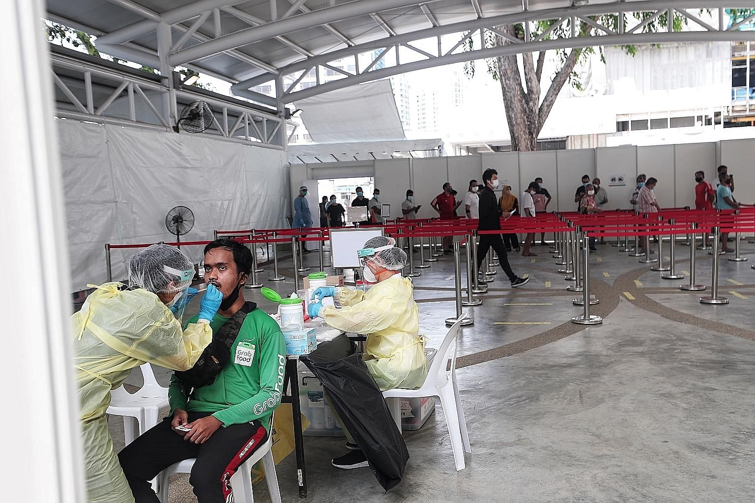 Top: Grab rider Muhd Raidan, 29, getting tested for Covid-19 at a temporary swabbing centre at the pavilion beside Block 75 Marine Drive yesterday. Above: Temasek chief executive Ho Ching and Emeritus Senior Minister Goh Chok Tong observing the testi