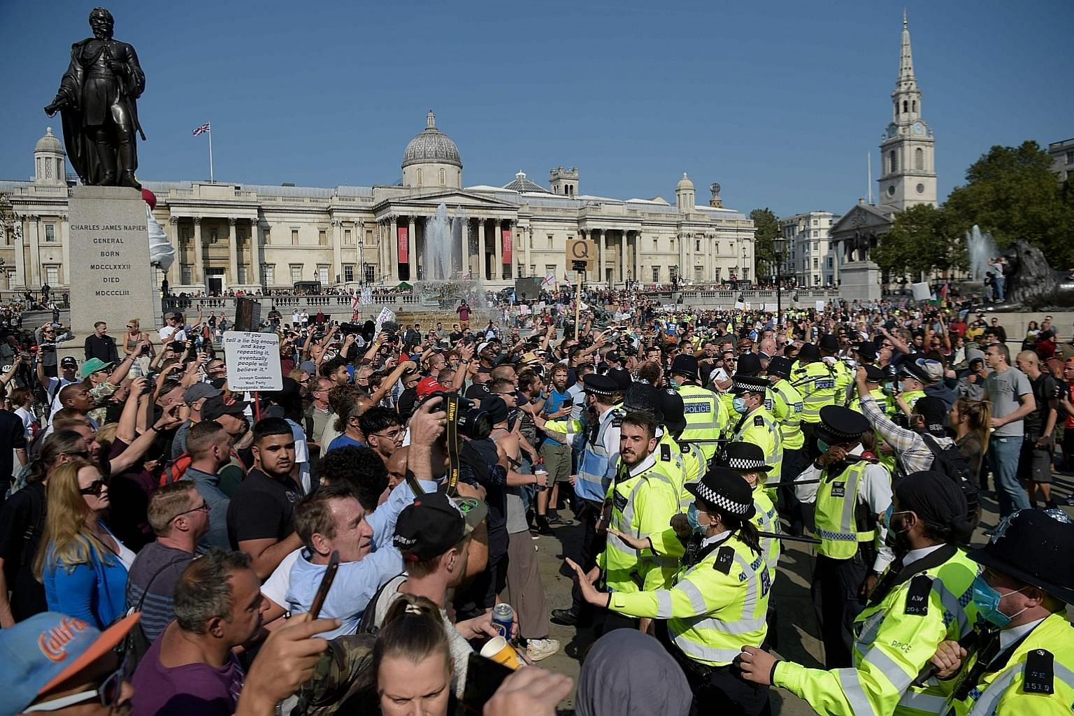 Police holding back protesters at an anti-vax rally in central London yesterday. The UK's official number of new positive cases shot up by nearly 1,000 on Friday to 4,322, the highest since May 8.
