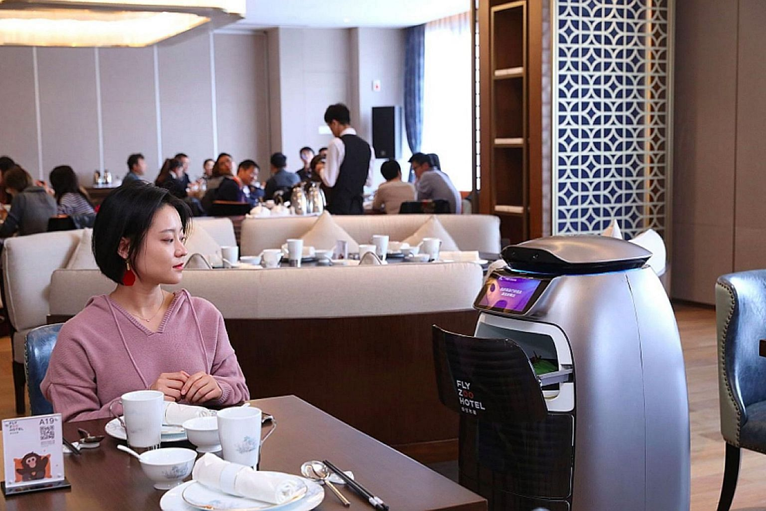 A diner being served by a robot in a restaurant at the FlyZoo Hotel in Hangzhou, China.