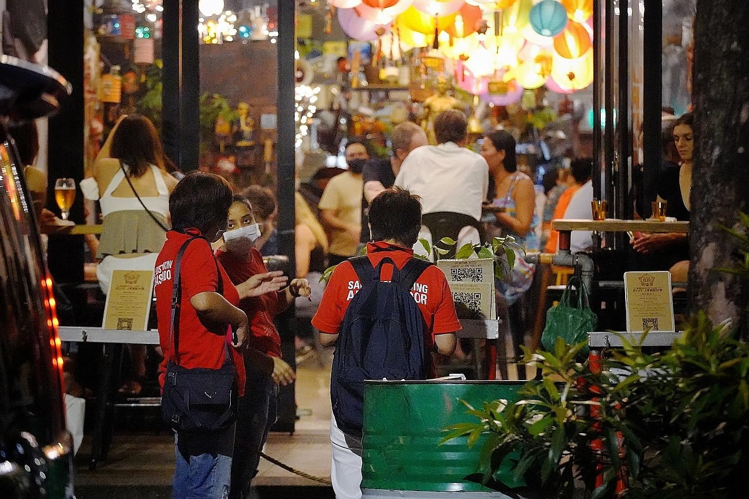 Safe distancing ambassadors speaking to a staff member of a restaurant in Telok Ayer Street on Friday.
