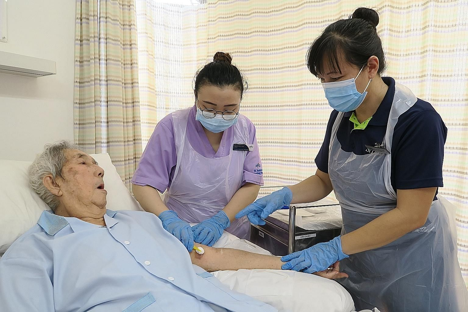 Assistant nurse clinician Caroline Tan (at right) from St Luke's Hospital training staff nurse Naqiyah Yusuf at St Andrew's Nursing Home (Taman Jurong) in wound care. St Luke's will use the Lew Foundation grant to extend its wound care expertise to t