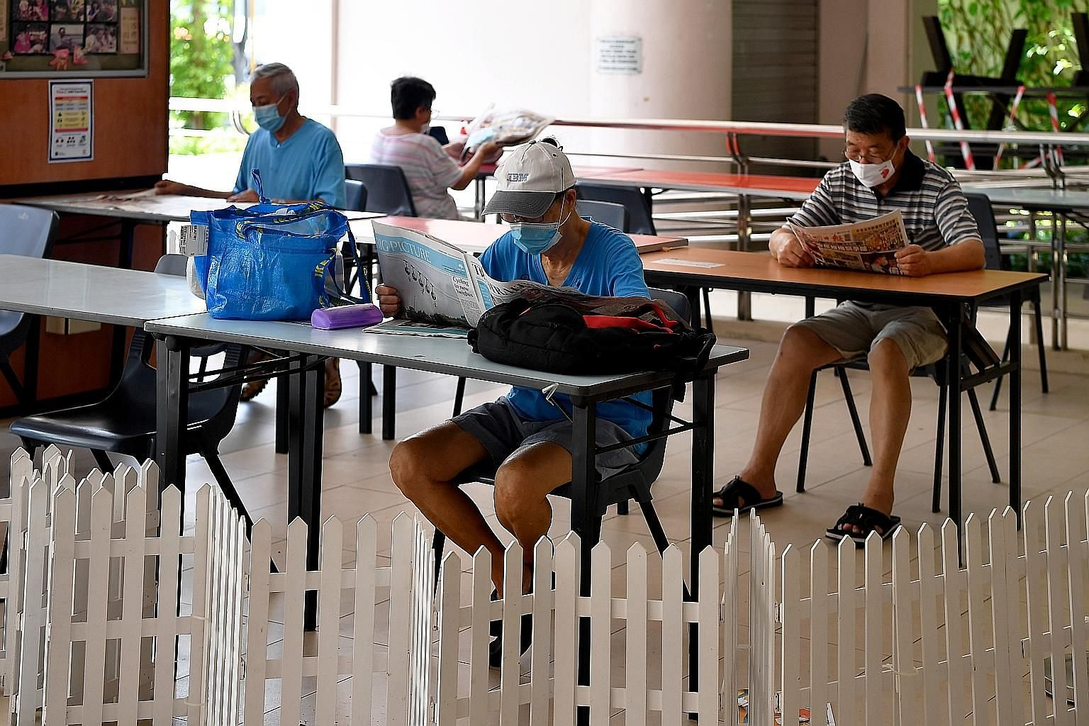 People reading newspapers at the Pasir Ris East Community Building last Friday. While there were no new cases in the community, Singapore recorded nine new imported cases.
