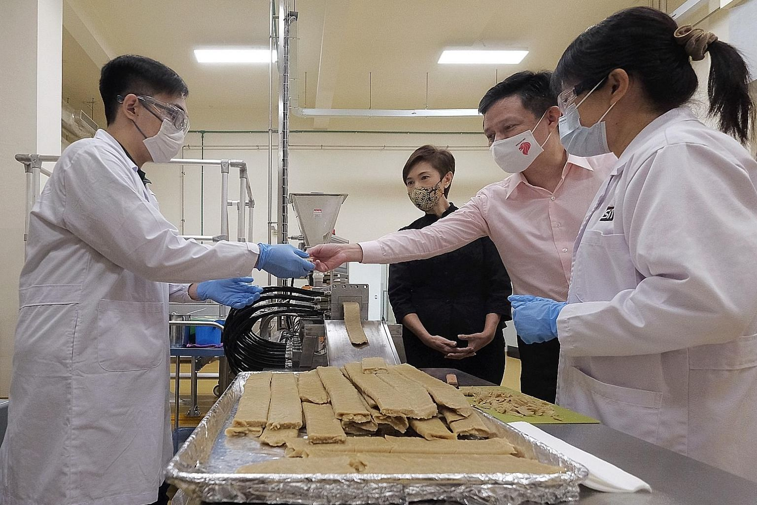 Minister for Trade and Industry Chan Chun Sing and Minister for Manpower Josephine Teo watching as an extruder machine made mock meat during a tour of food manufacturer KH Roberts' facility yesterday. The food manufacturing and service industry is ex