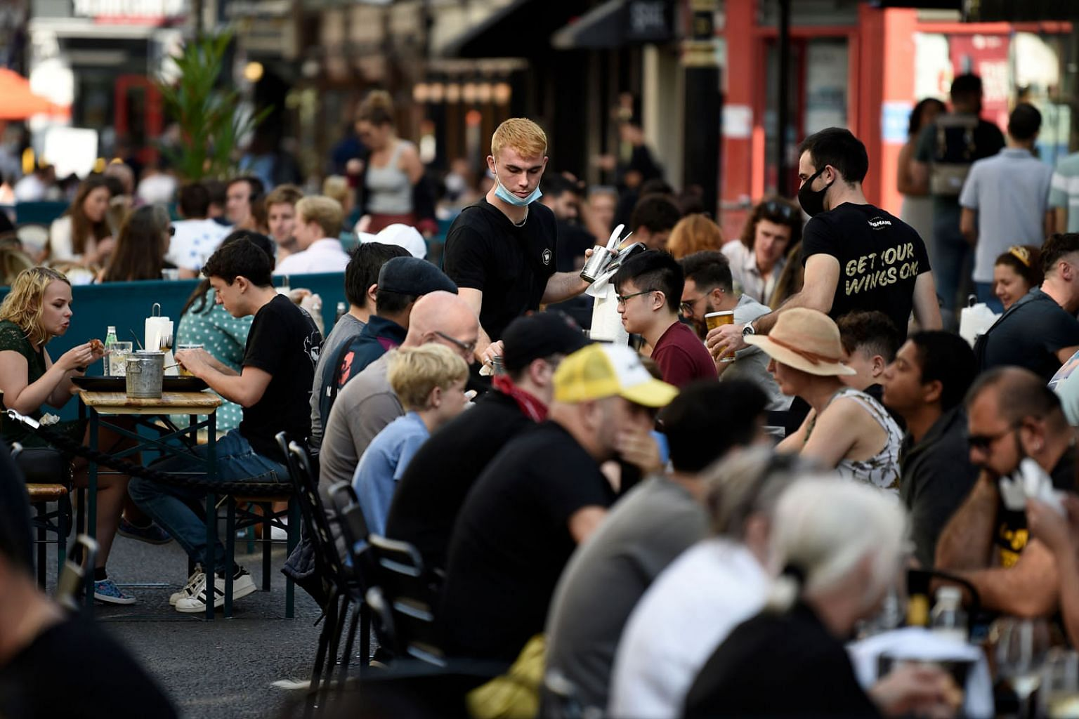 Left: Diners at a restaurant in London. Medical experts say that with winter approaching, the Covid-19 problem would haunt Britain for another six months at least. The country has the highest official Covid-19 death toll in Europe - and the fifth-lar