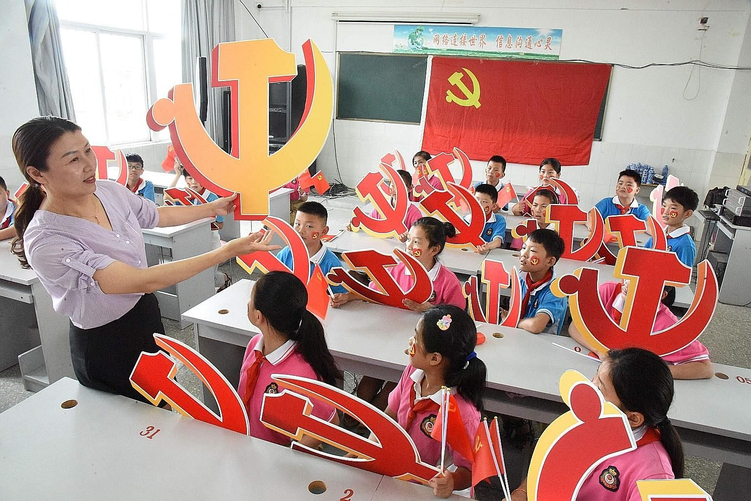 A teacher and her pupils with Chinese Communist Party emblems at a school in eastern Jiangsu province. The writer says the West is labouring under three flawed assumptions, one of which is that China cannot possibly be a good partner as long as it is
