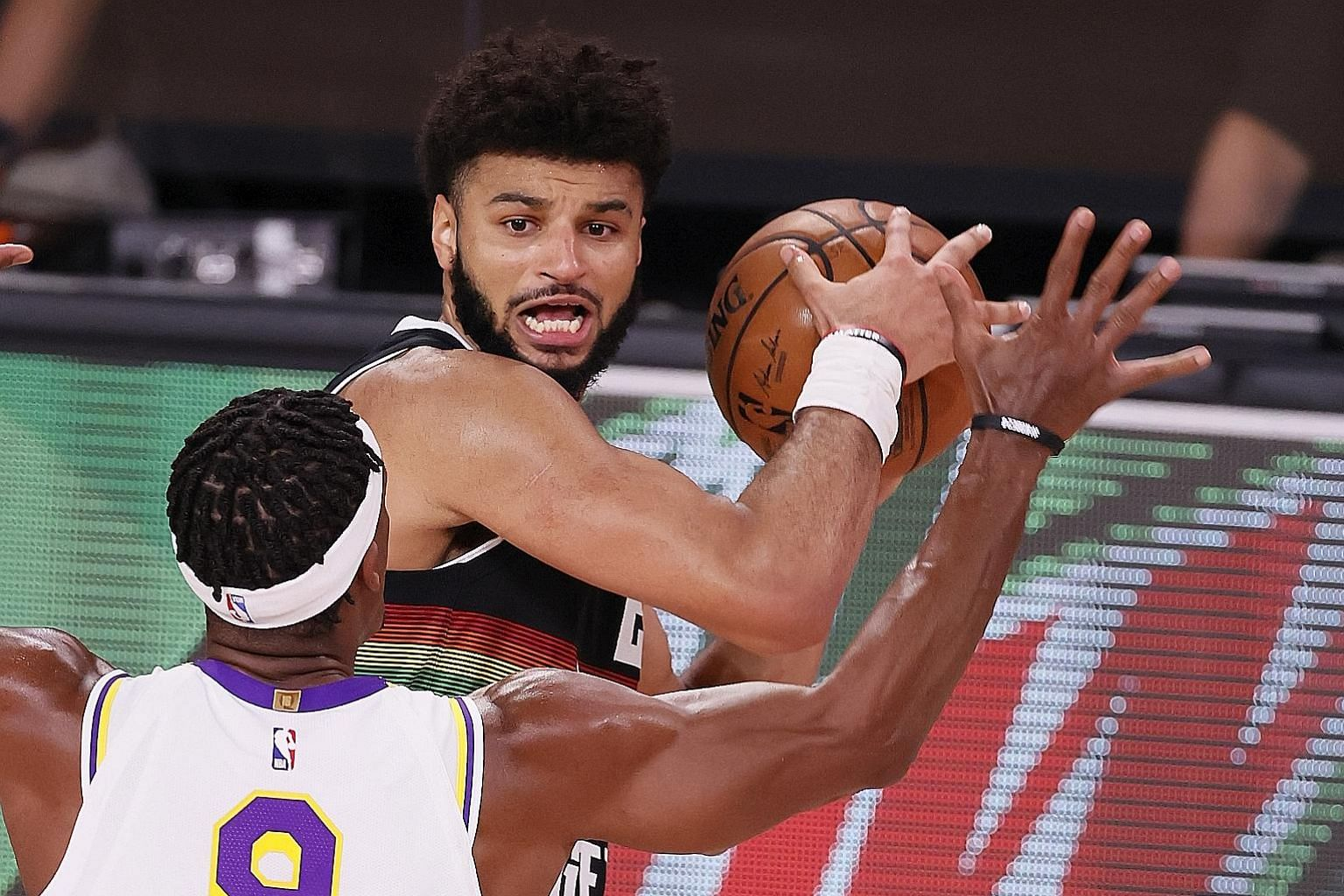 Denver guard Jamal Murray looking to pass around LA Lakers guard Rajon Rondo in Game 3 of the Western Conference Finals in Kissimmee, Florida on Tuesday. He scored 28 points in his side's 114-106 win.