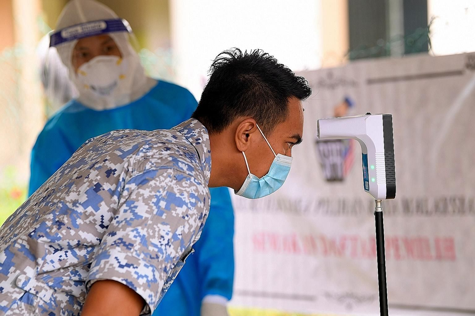 A member of the Malaysian military having his temperature checked before being able to cast his ballot during early voting in the Sabah state election on Tuesday. PHOTO: BERNAMA