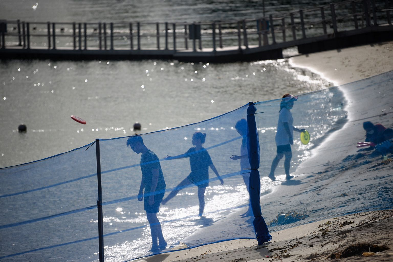 People playing with frisbees behind a barrier separating different sections of Siloso Beach on Sentosa last Wednesday. On why many people are planning to use their tourism vouchers on attractions and staycations, Dr Michael Chiam, a senior tourism le