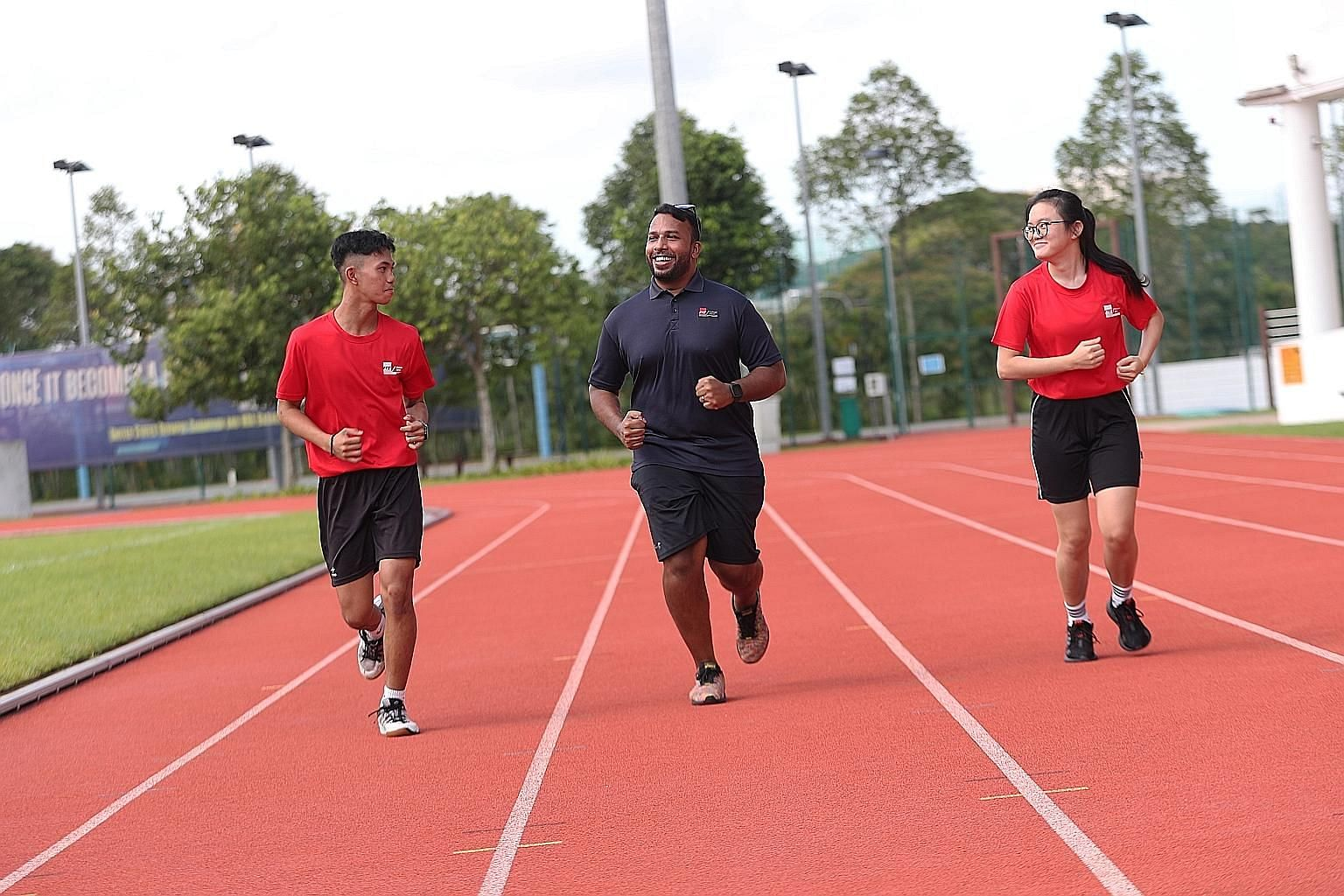 Physical education lecturer Mark Daniel running with Mikhail Raiyan, a second-year Nitec student in electrical engineering, power and control, and Ng Li Yan, in her first year in the Nitec travel and tourism services course. ST PHOTO: TIMOTHY DAVID
