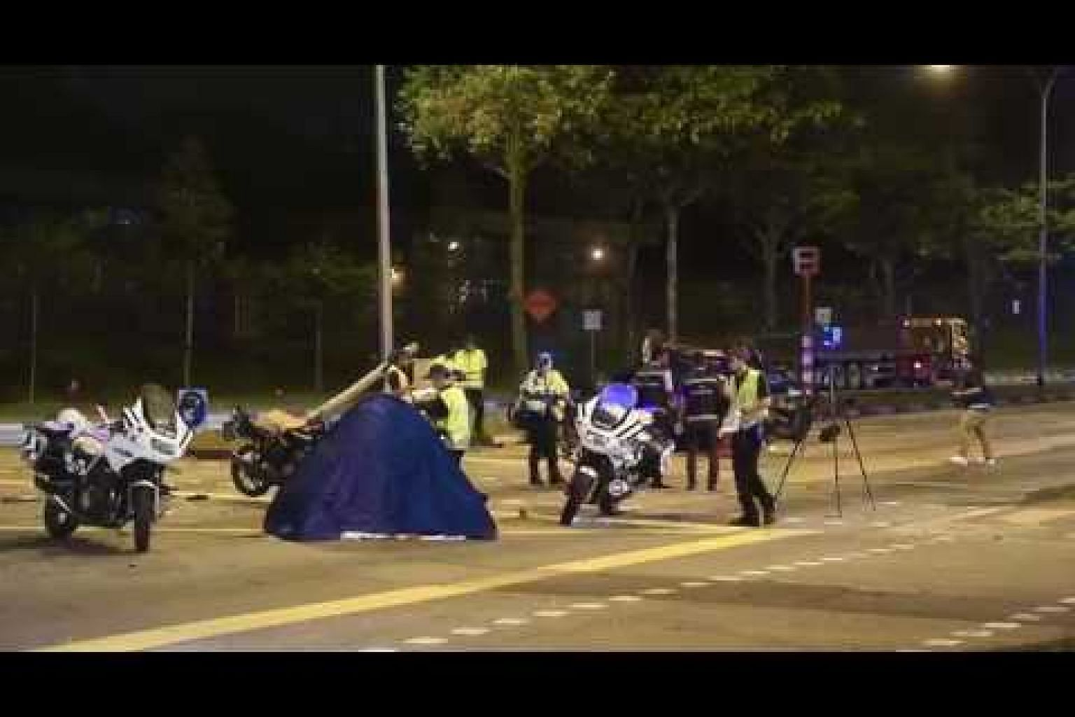 Police officers at the site of the accident in Woodlands Avenue 12.