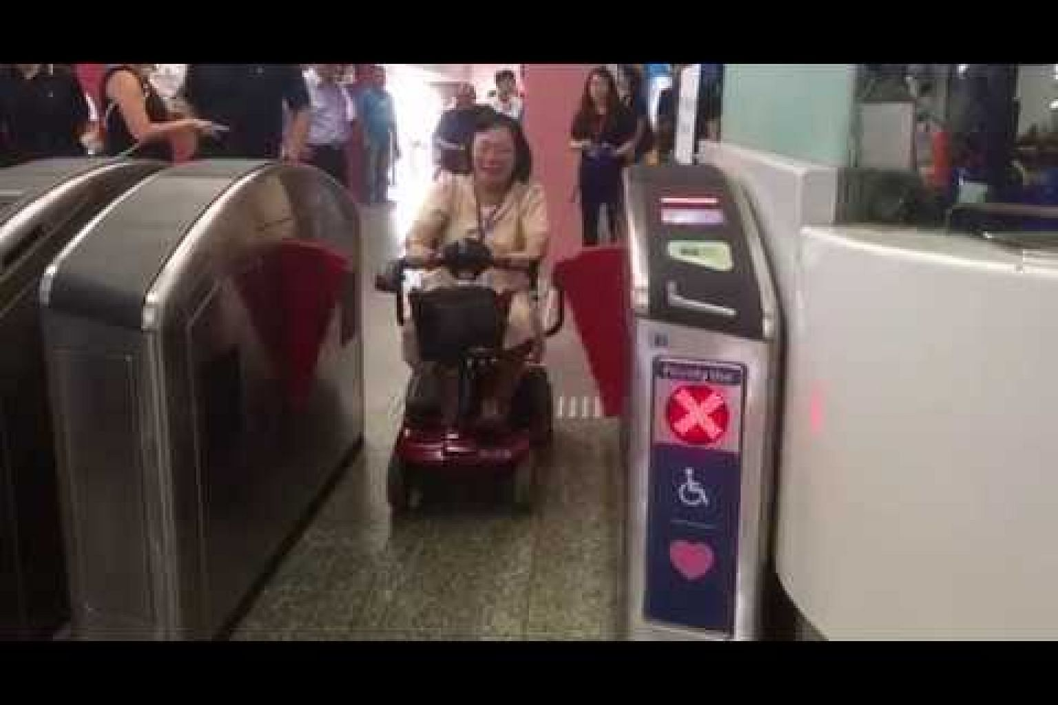 Commuters in wheelchairs enter the hands-free fare gate at Redhill MRT station