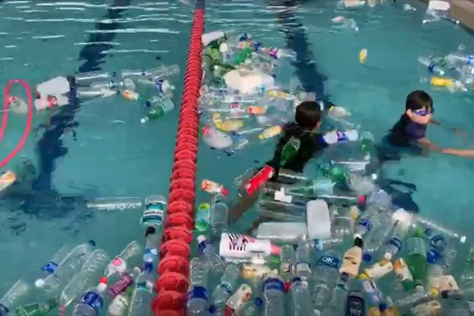 Students swim in plastic-filled swimming pool