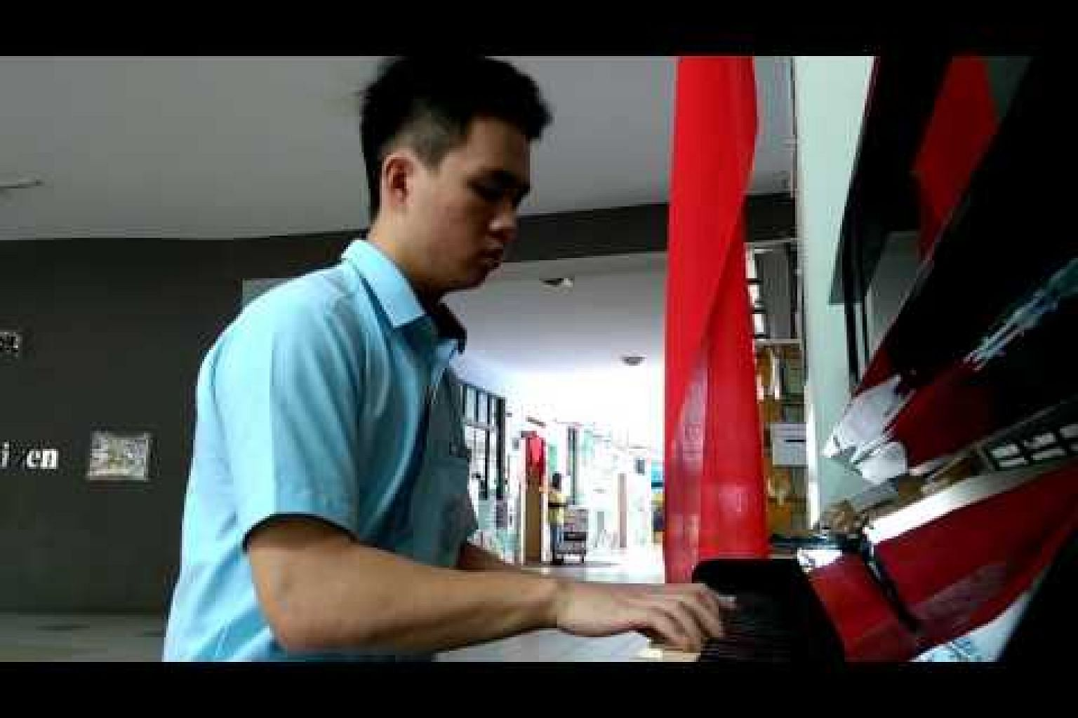 Self-taught pianist Tan Ou Wen playing on the school piano