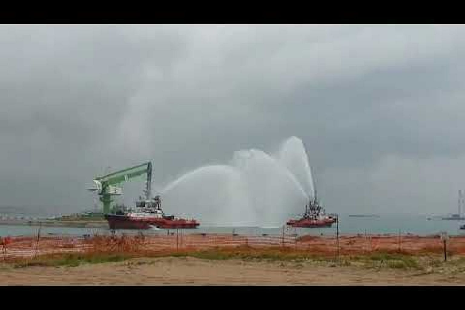 Water cannons fire off at the location of the future Tuas port