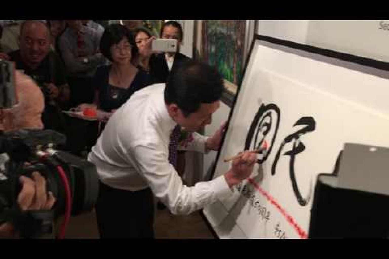 Ong Ye Kung completing a calligraphy piece by Dr Ho Kah Leong