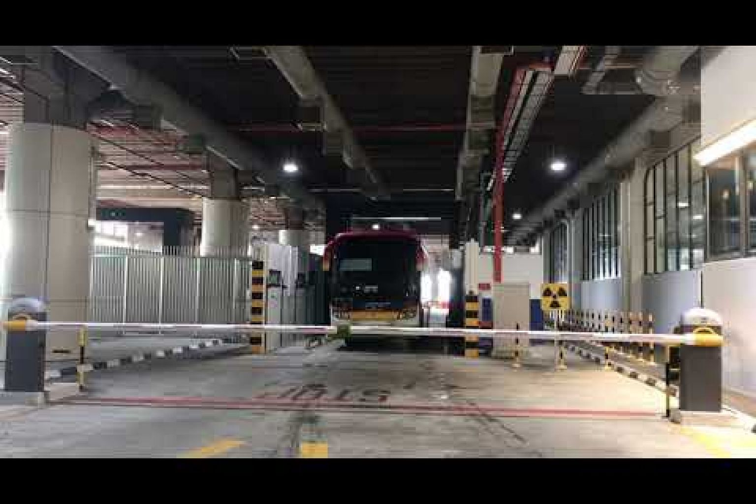 Passenger bus passes through an imaging scanner at Tuas Checkpoint