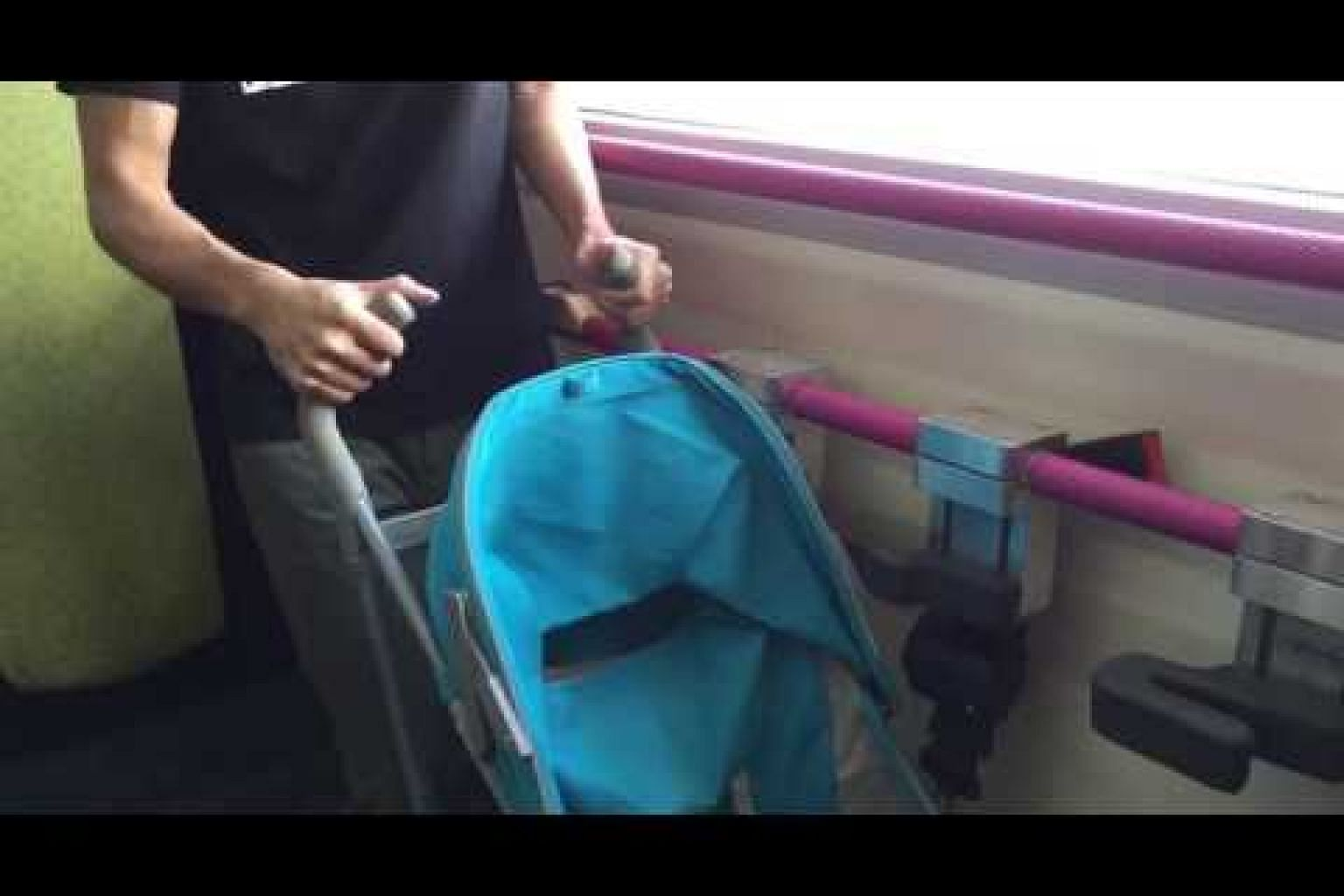 Demo on the use of the restraining device meant to help secure baby strollers in buses