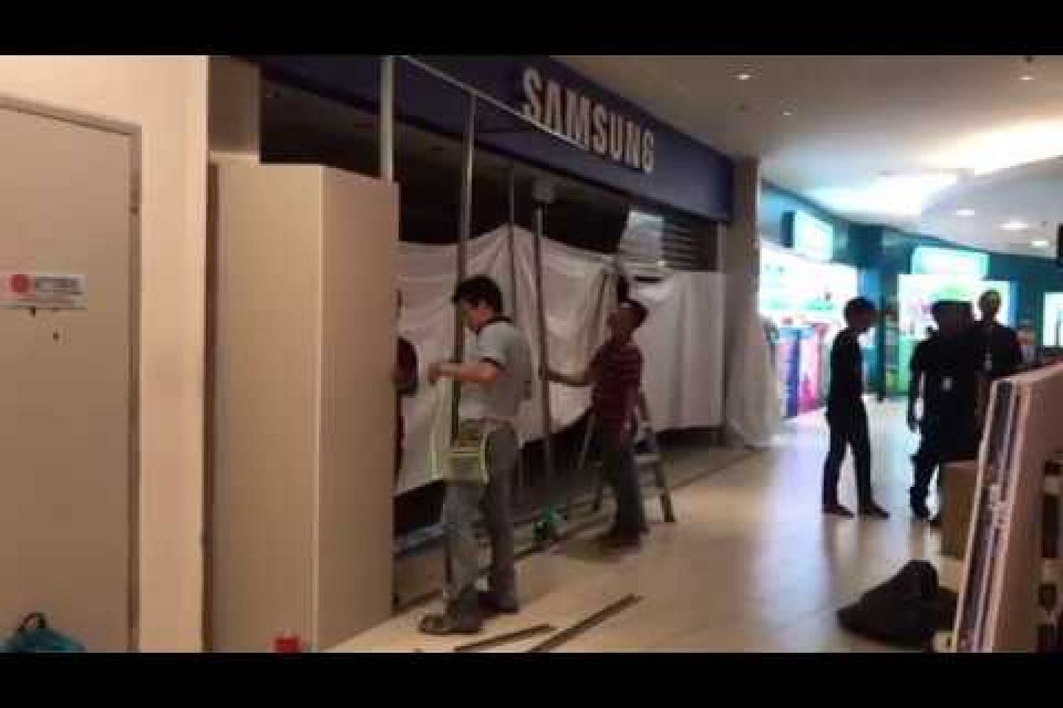 Workers cleaning up Samsung store at AMK Hub