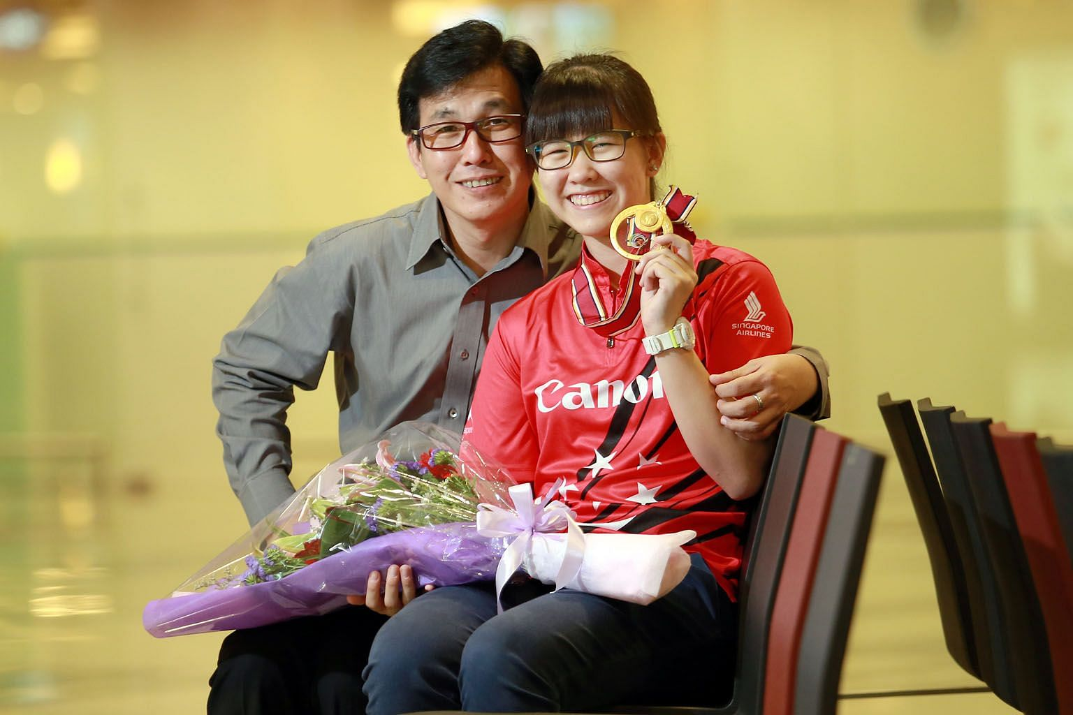 Inaugural Bowling World Open champion Joey Yeo is received by her proud dad Jeffrey, 49, at the airport.