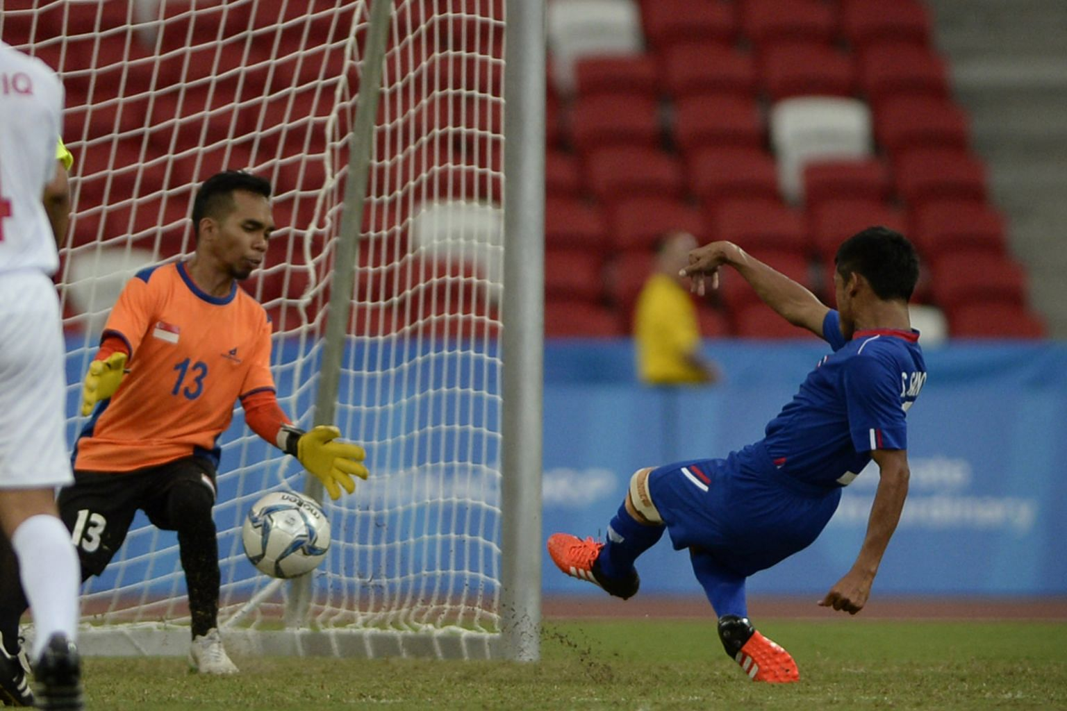 Thailand's Sanya Suksang (left) scoring past Singapore goalkeeper Firdaus Nor. The Thais played attacking football and Sanya netted twice in the 5-0 win.