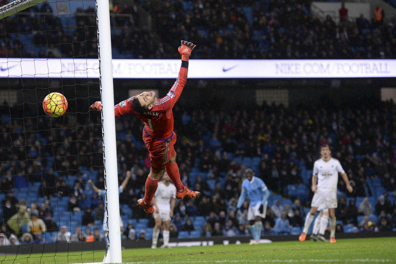 Swansea City goalkeeper Lukasz Fabianski fails to stop the match-winner from Manchester City's Yaya Toure (middle) in the Premier League match on Saturday. Toure's goal sealed a dramatic, stoppage-time 2-1 victory for City, who had let in the equalis