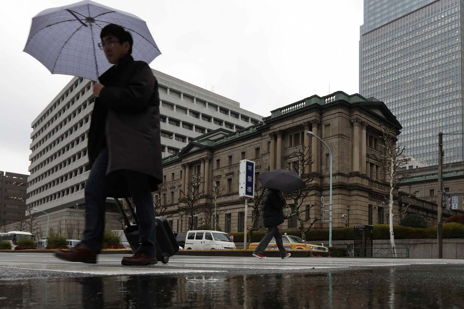 The Bank of Japan's headquarters in Tokyo. The BOJ's move to join the European Central Bank and others in driving their key benchmark interest rates to below zero helped drive the Dow up 2.5 per cent last Friday.