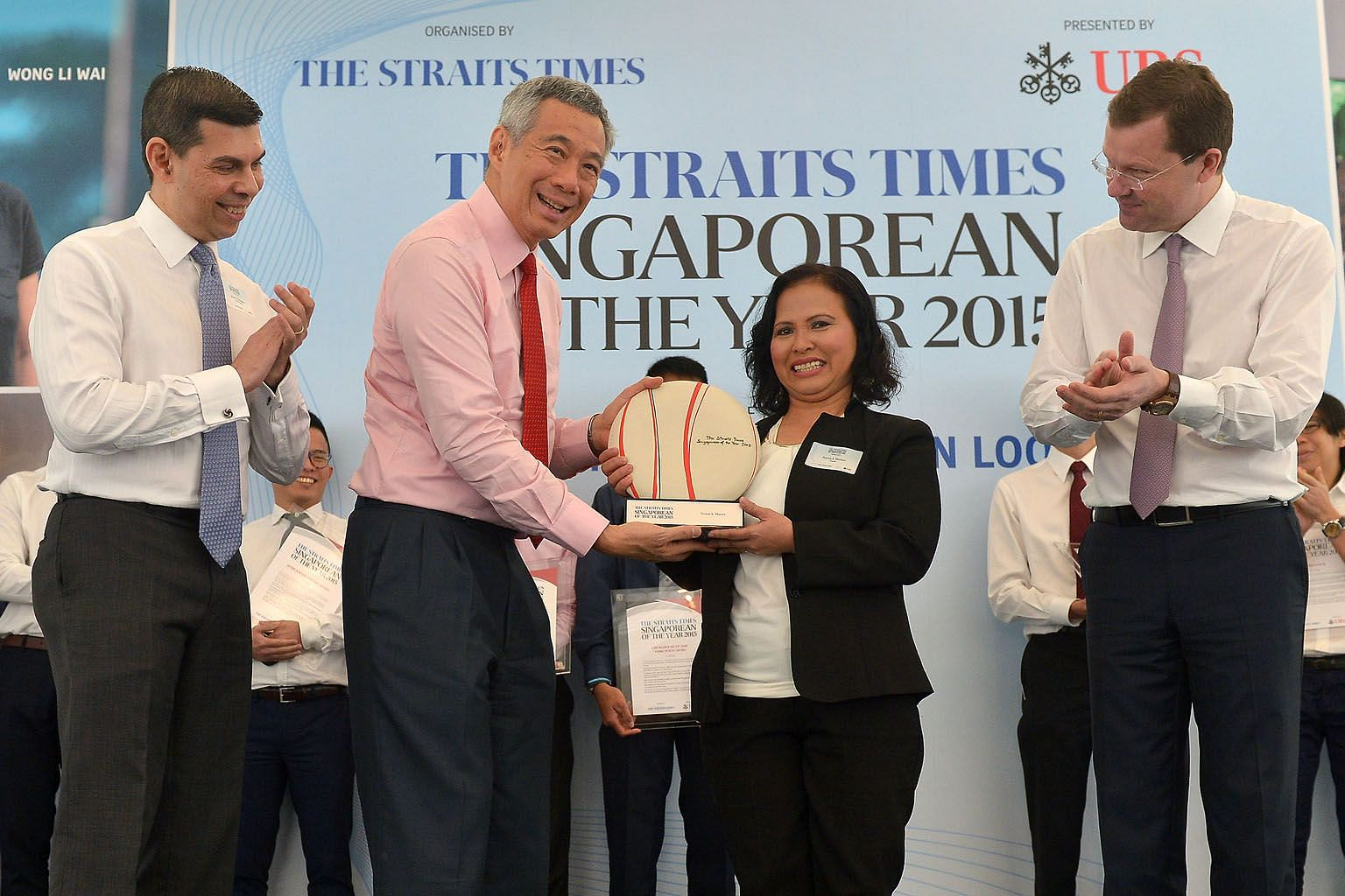 PM Lee presenting Madam Noriza with the Singaporean of the Year trophy at the UBS Business University yesterday. With them are Straits Times Editor Warren Fernandez (left) and Mr Juerg Zeltner, president of UBS Wealth Management. Madam Noriza hopes h