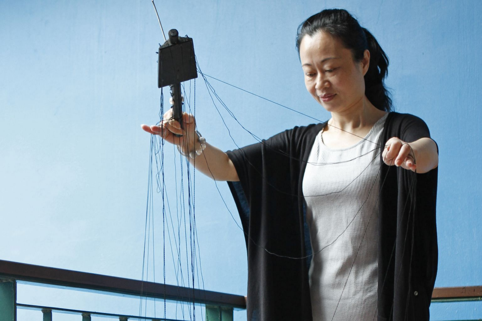 Leading Chinese puppeteer Zhuang Lie, manipulates the 36 strings attached to each puppet with deft fingers.