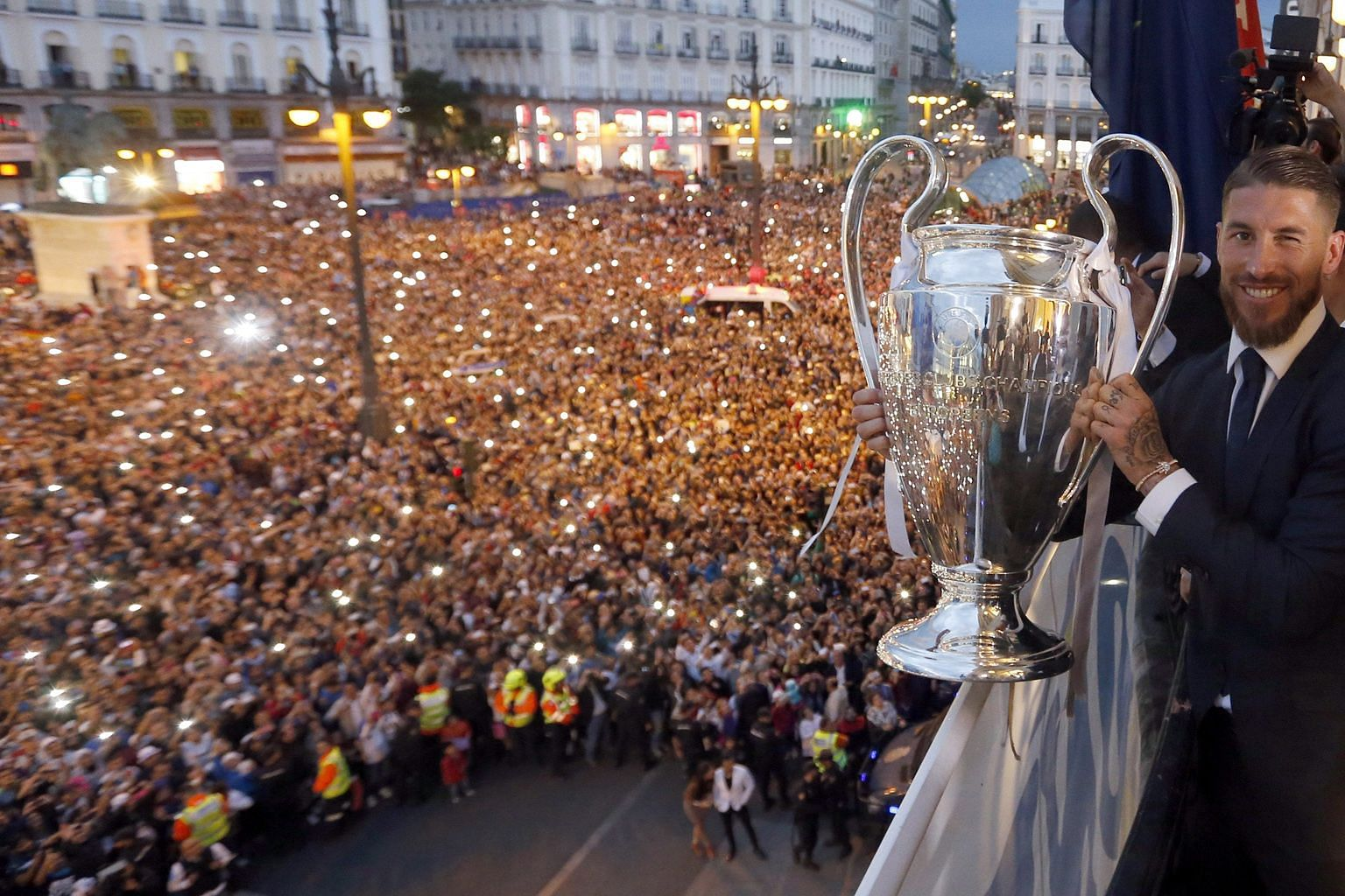 Real skipper Sergio Ramos holding the Champions League trophy on the balcony of the Madrid Autonomous Government's headquarters, as thousands of frenzied fans cheer during the celebrations.