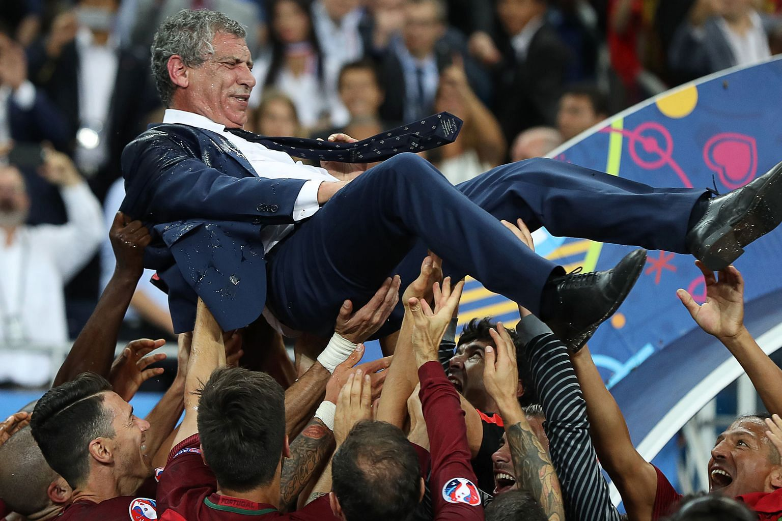 Portugal's coach Fernando Santos is tossed into the air by his players as they celebrate after beating France in the Euro final.