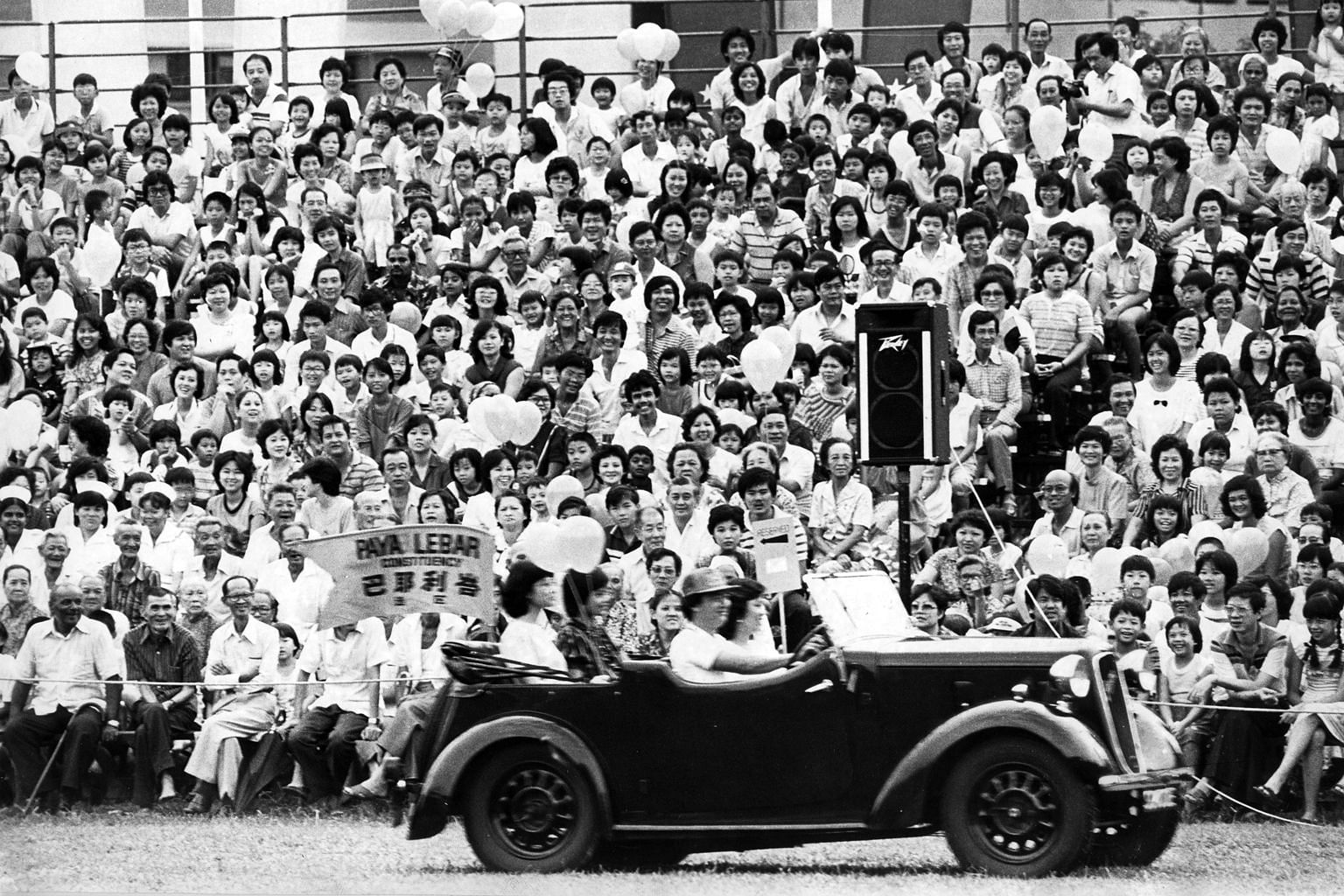 A contingent bearing a model of the MRT, a symbol of progress, at the parade in 1985. The massive transport project, green-lighted by the Government in 1982 after years of study, began operations in November 1987. Above: A vintage Austin 7 chugging p