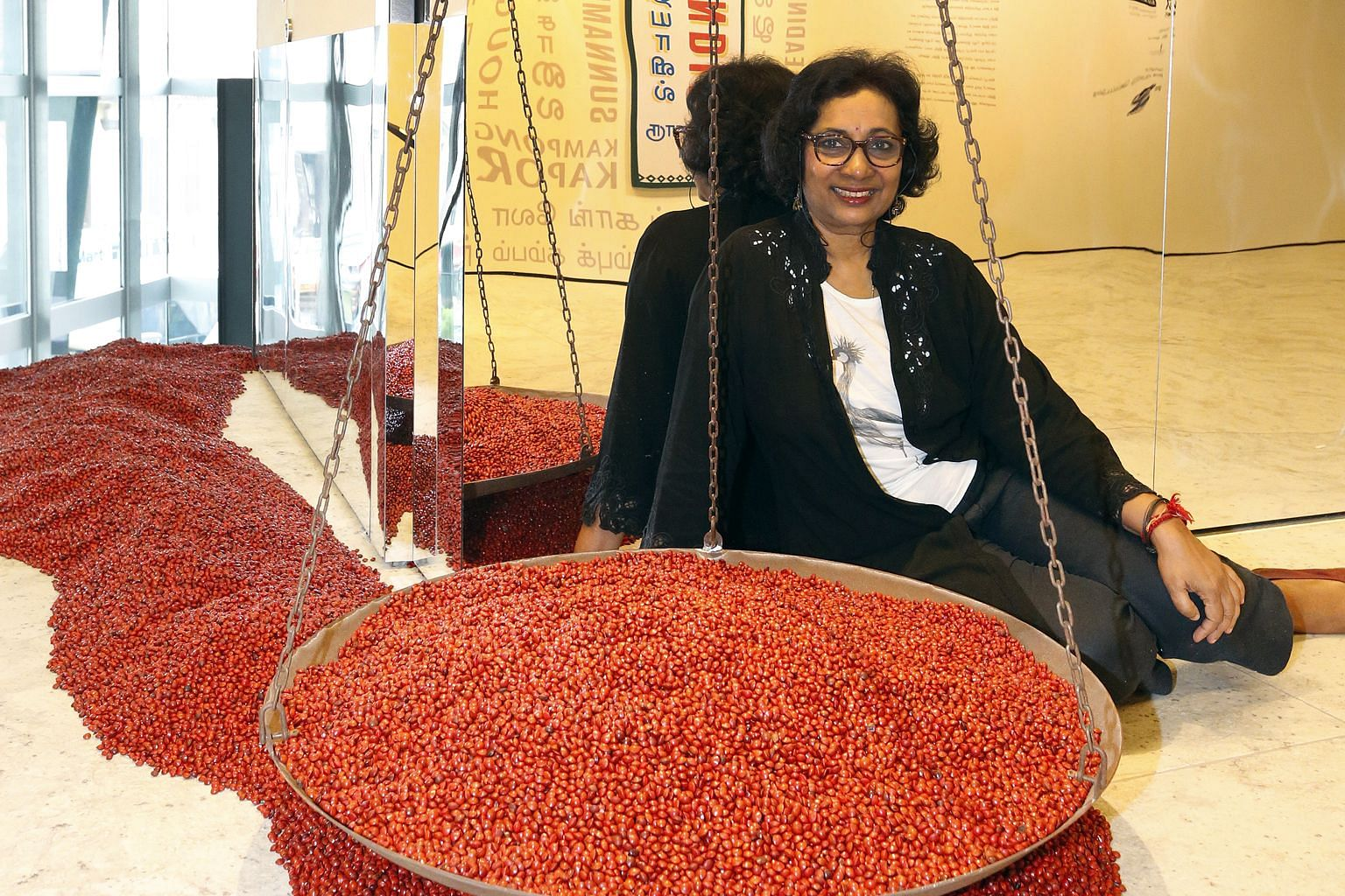 Artist Kumari Nahappan with her art installation, The Weighing Scales, at the Indian Heritage Centre.