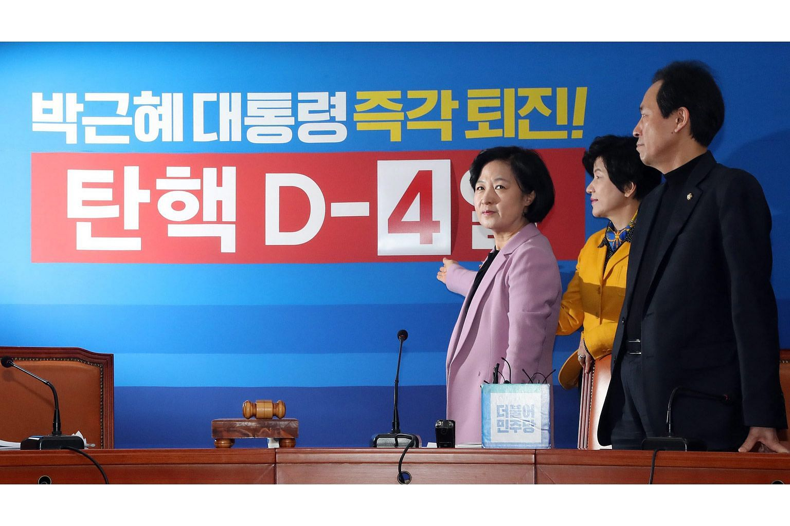 Ms Choo Mi Ae (far left), head of South Korea's main opposition Democratic Party, indicating a poster counting down to voting day on the motion to impeach President Park Geun Hye yesterday.