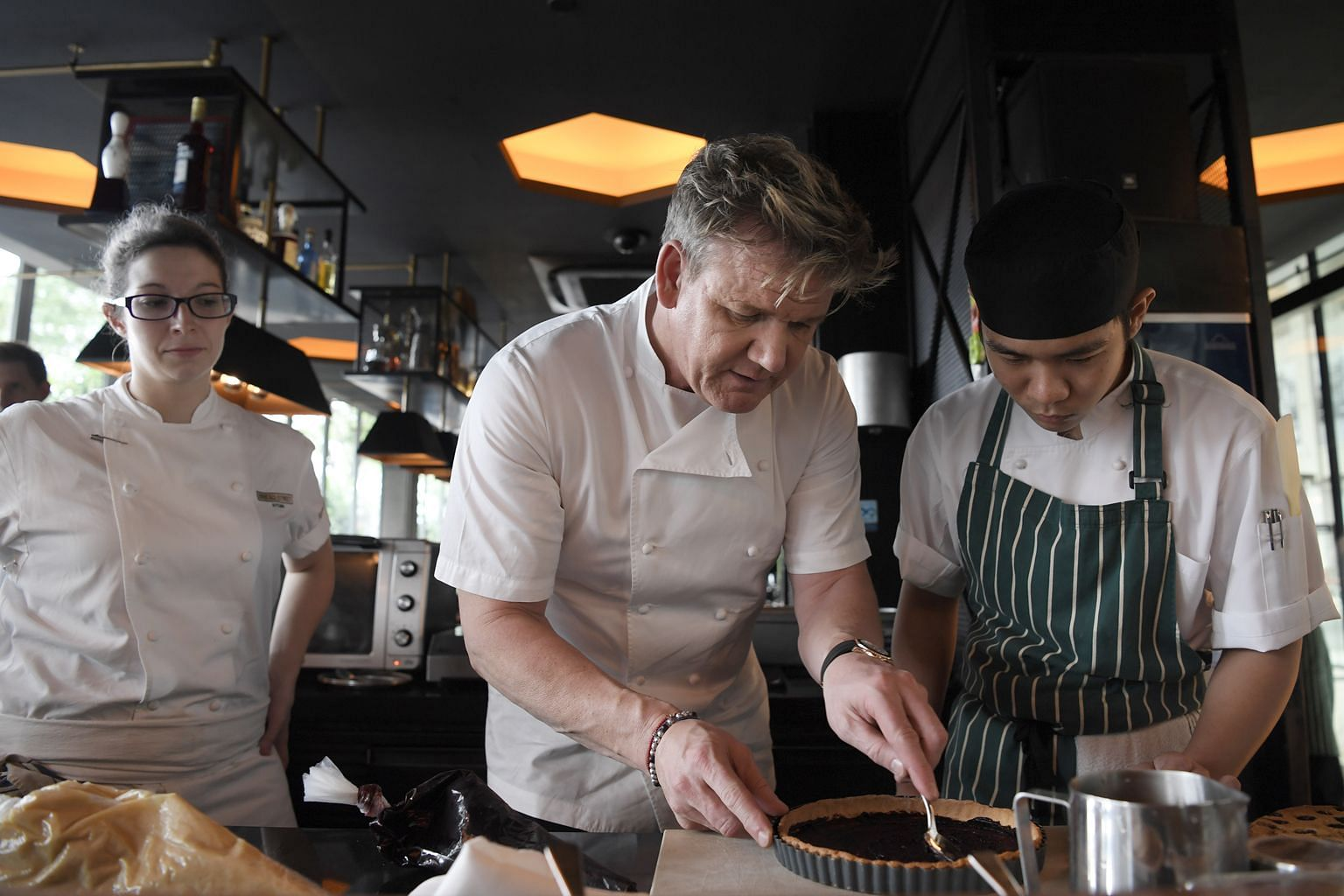 British restaurateur Gordon Ramsay shows Bread Street Kitchen intern Ong Sao Wee how to spread blueberry paste for the blueberry- almond tart creme fraiche. Standing behind them is the restaurant's executive chef Sabrina Stillhart.