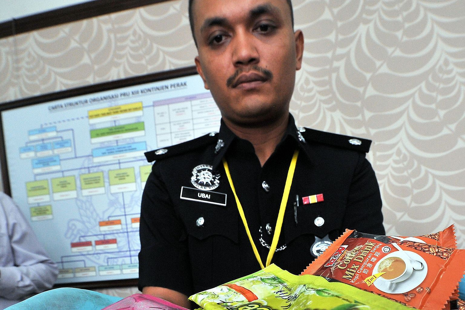 Investigating officer in the Manjung narcotics crime department Mohd Ubaidillah Kamaruzan with sachets of instant coffee and powdered drink used by drug syndicates to package ketamine. The syndicate was busted in a raid at an entertainment centre in