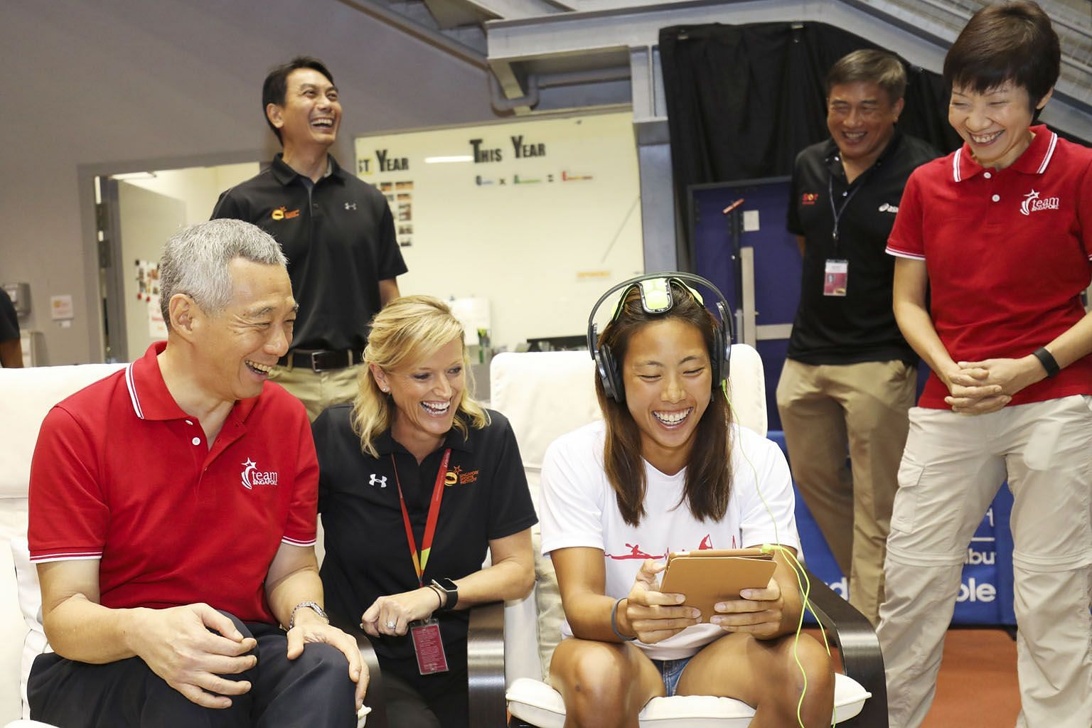 Prime Minister Lee Hsien Loong and SSI head of sport psychology Tracey Veivers watch as kayaker Sarah Chen shows how the iPad and Versus headset are used to help athletes with their mental conditioning. Behind them are Dr Frankie Tan (left), principa