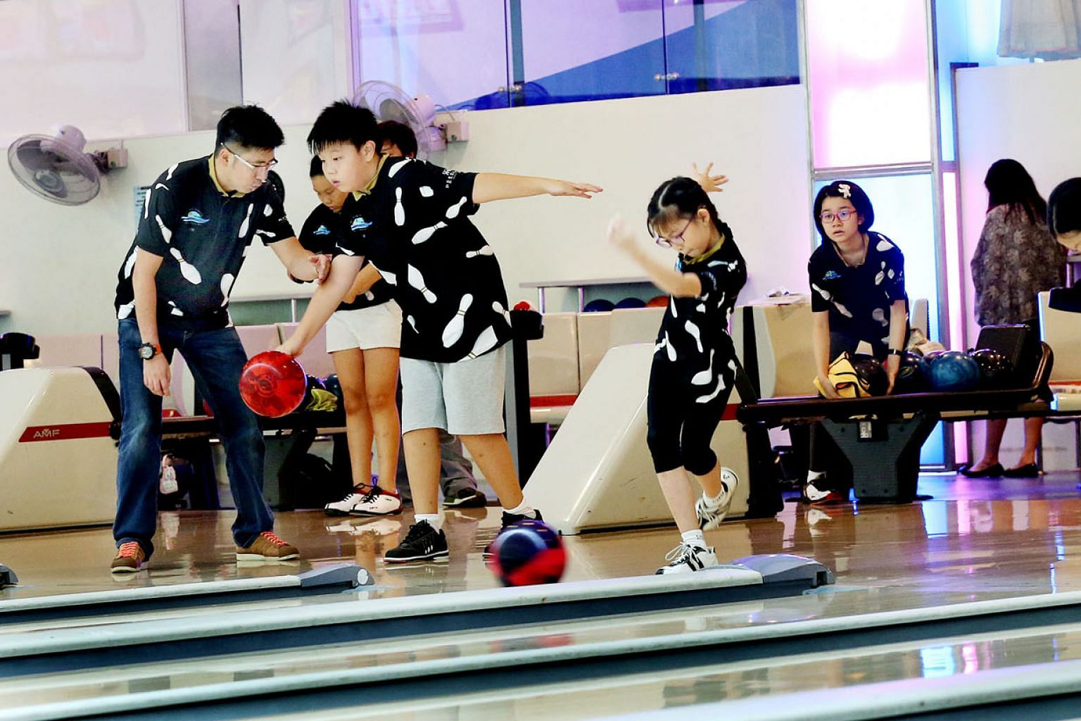Ex-world champion bowler Remy Ong showing youngsters how to deliver the ball. He says ex-sportsmen are aware not only of the technical skills needed to succeed but also the mental strength required.