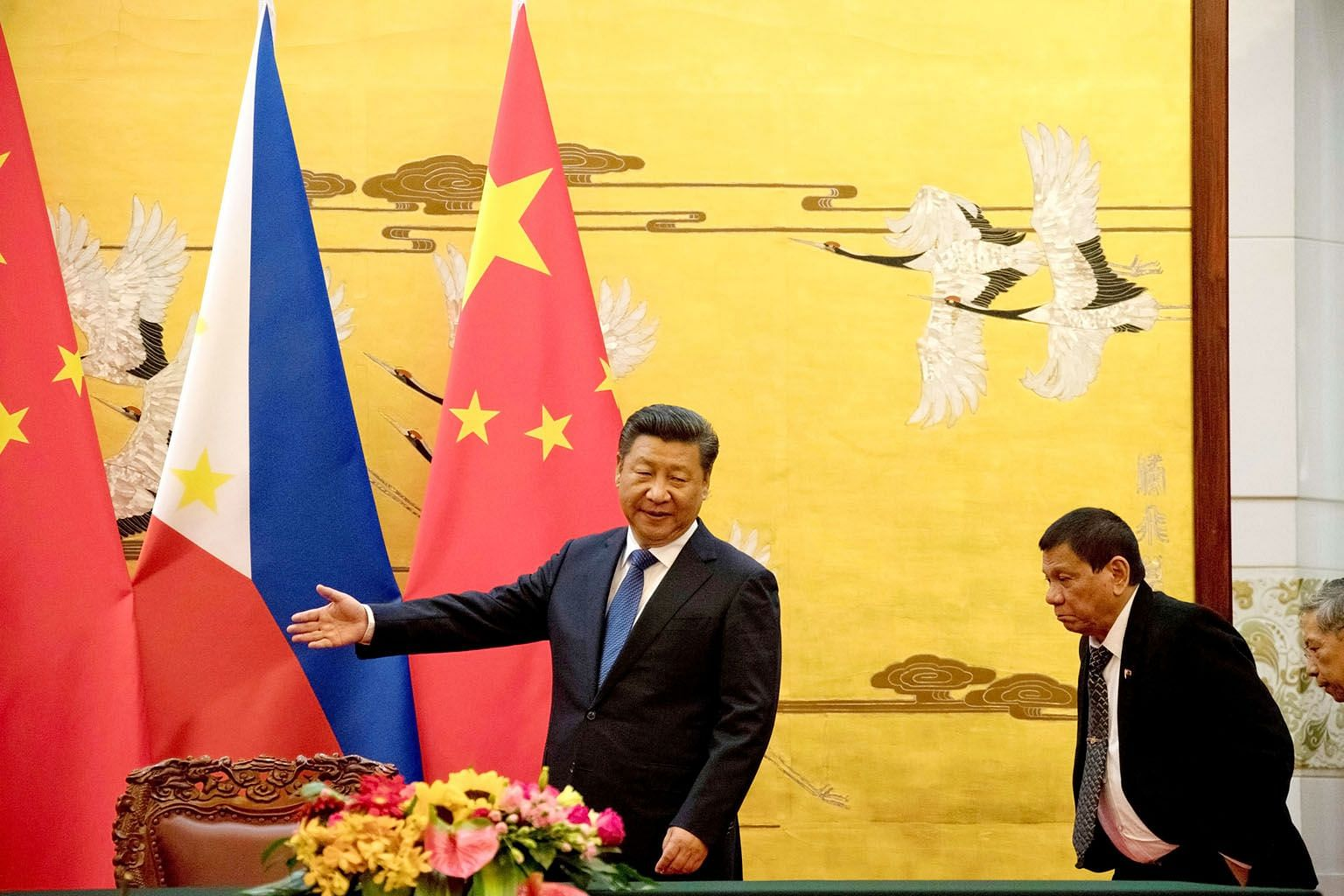 Chinese President Xi Jinping showing Philippine President Rodrigo Duterte the way at a signing ceremony in Beijing in October last year. President Duterte's rapprochement with China is faltering: Chinese capital has not poured into the Philippines, n