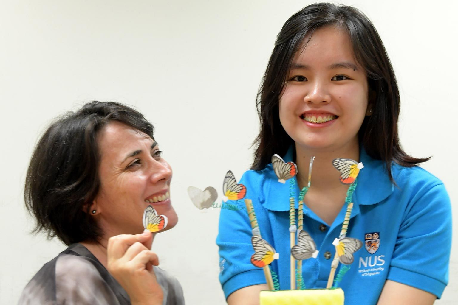 NUS PhD student Jocelyn Wee and her supervisor Antonia Monteiro with the butterfly models she used during the study. Ms Wee found that red appeared to be more effective than yellow in keeping predators at bay.