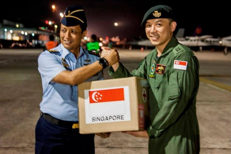 Singapore Armed Forces Mission Commander Oh Chun Keong (right) handing over the relief package to Lt-Col Ali Sudibyo, of the Indonesian Armed Forces at Balikpapan Airport, Indonesia (3 Oct). Image: MINDEF
