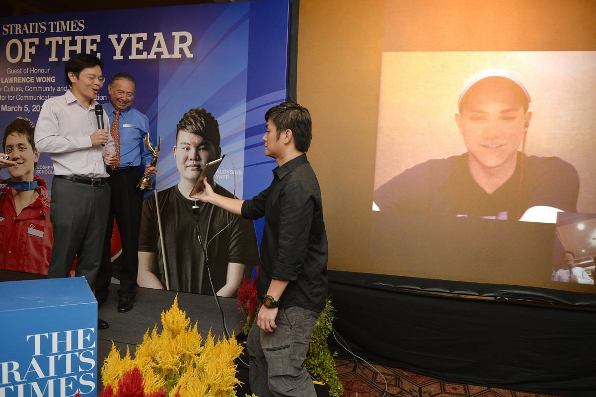 The Straits Times Athlete of the Year Joseph Schooling waves to the crowd through a Skype conversation after his father Colin (centre, in blue) accepted the award on his behalf from Minister for Culture, Community and Youth Lawrence Wong on March 5,