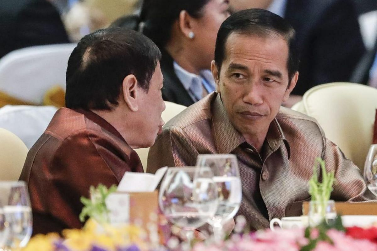 Philipinnes President Rodrigo Duterte (left) listens to Indonesia's President Joko Widodo (right) during the gala dinner at the 28th and 29th Asean Summits at the National Convention Centre in Vientiane, Laos, on Sept 7, 2016.